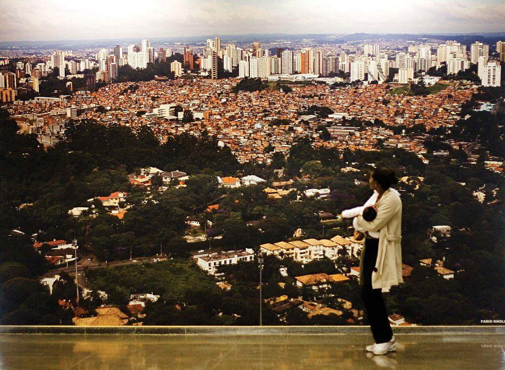 A woman holding a child observes a photo of the city of São Paulo in 1979, which shows a view of the region where the Penthouse Building is located.
